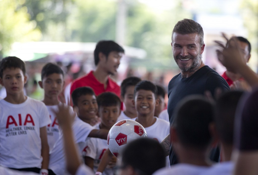 Retired footballer David Beckham holding a soccer ball in his hand smilies during a sponsored promotional event in Bangkok, Thailand, Saturday, Nov 3,...