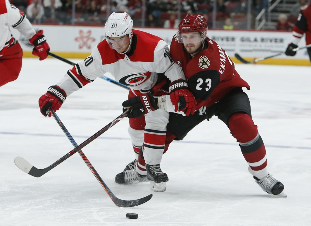 Carolina Hurricanes center Sebastian Aho (20) and Arizona Coyotes defenseman Oliver Ekman-Larsson vie for the puck during the second period of an NHL ...