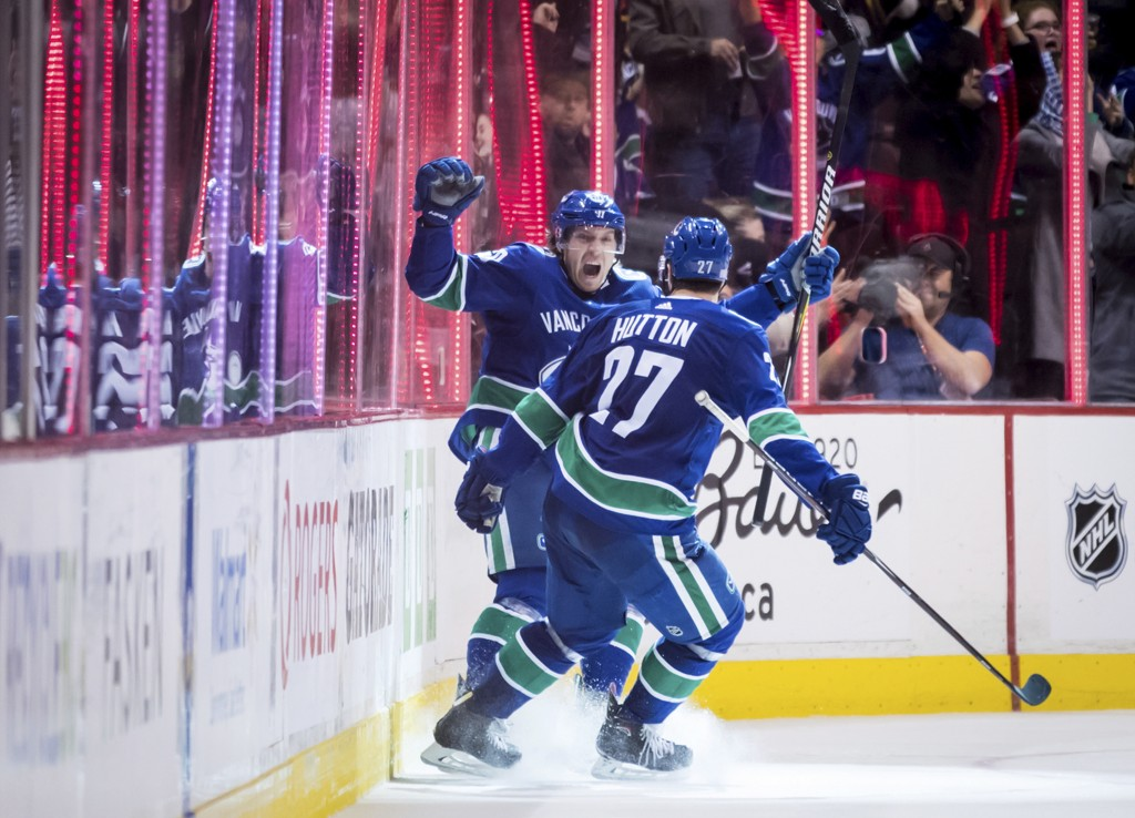 Vancouver Canucks' Markus Granlund, back, of Finland, and Ben Hutton celebrate Granlund's goal against the Colorado Avalanche during the third period ...