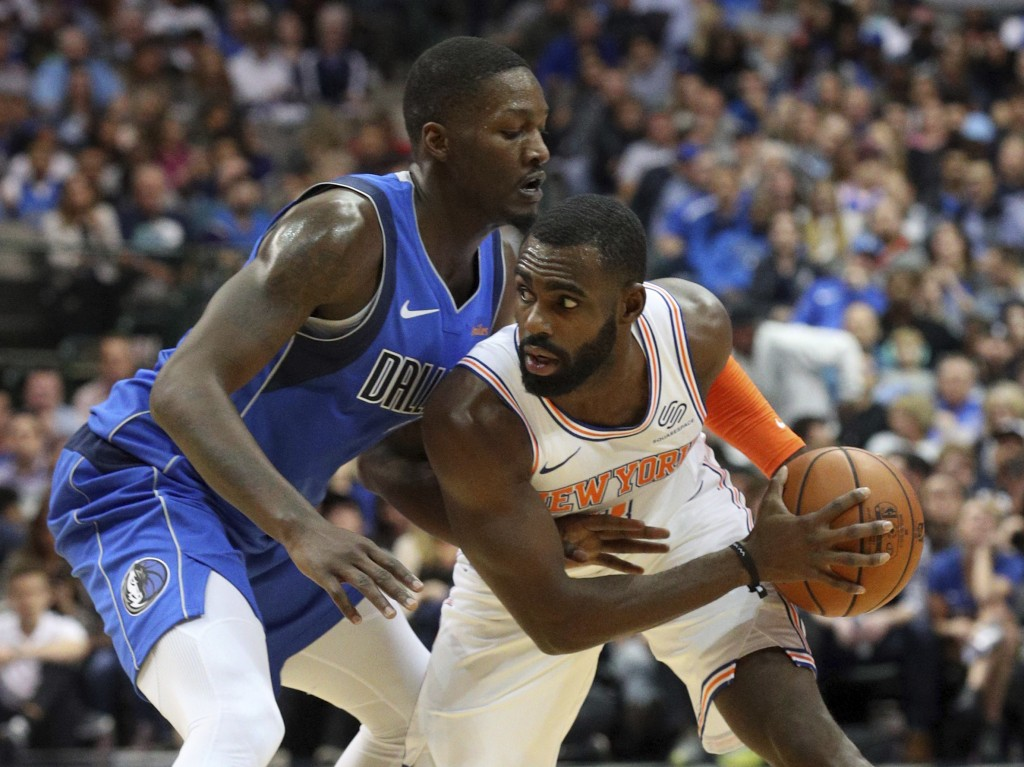 Dallas Mavericks forward Dorian Finney-Smith (10) defends as New York Knicks guard Tim Hardaway Jr. (3) looks for an opening in the first half of an N...