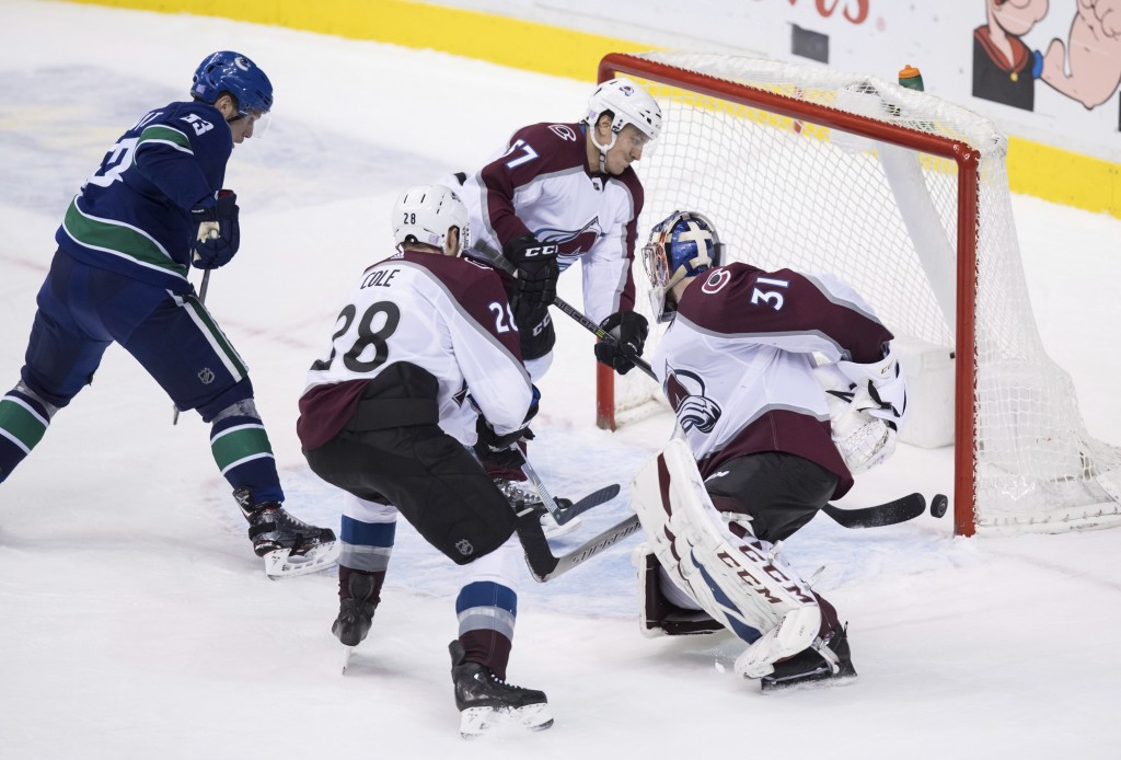 Colorado Avalanche left wing Gabriel Bourque (57), defenseman Ian Cole (28) and goalie Philipp Grubauer (31), of Germany, and Vancouver Canucks' Bo Ho...
