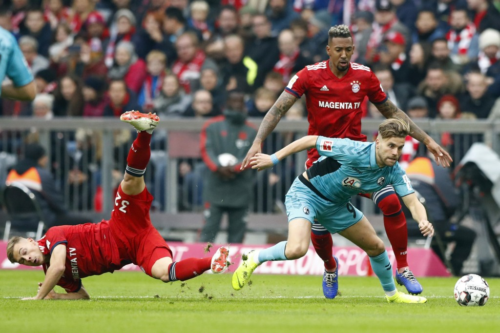 Bayern's Joshua Kimmich, left, Bayern's Jerome Boateng, background right, and Freiburg's Lucas Hoeler challenge for the ball during the German Bundesl