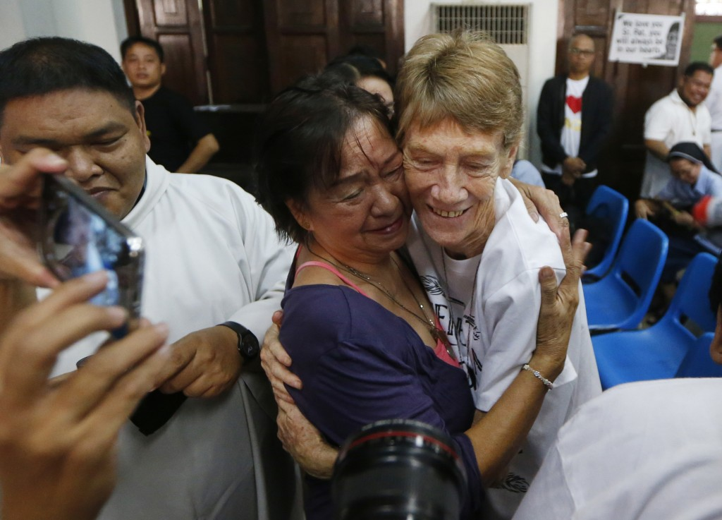 Australian Roman Catholic nun Sister Patricia Fox is hugged by a supporter following a news conference hours before her departure for Australia Saturd...