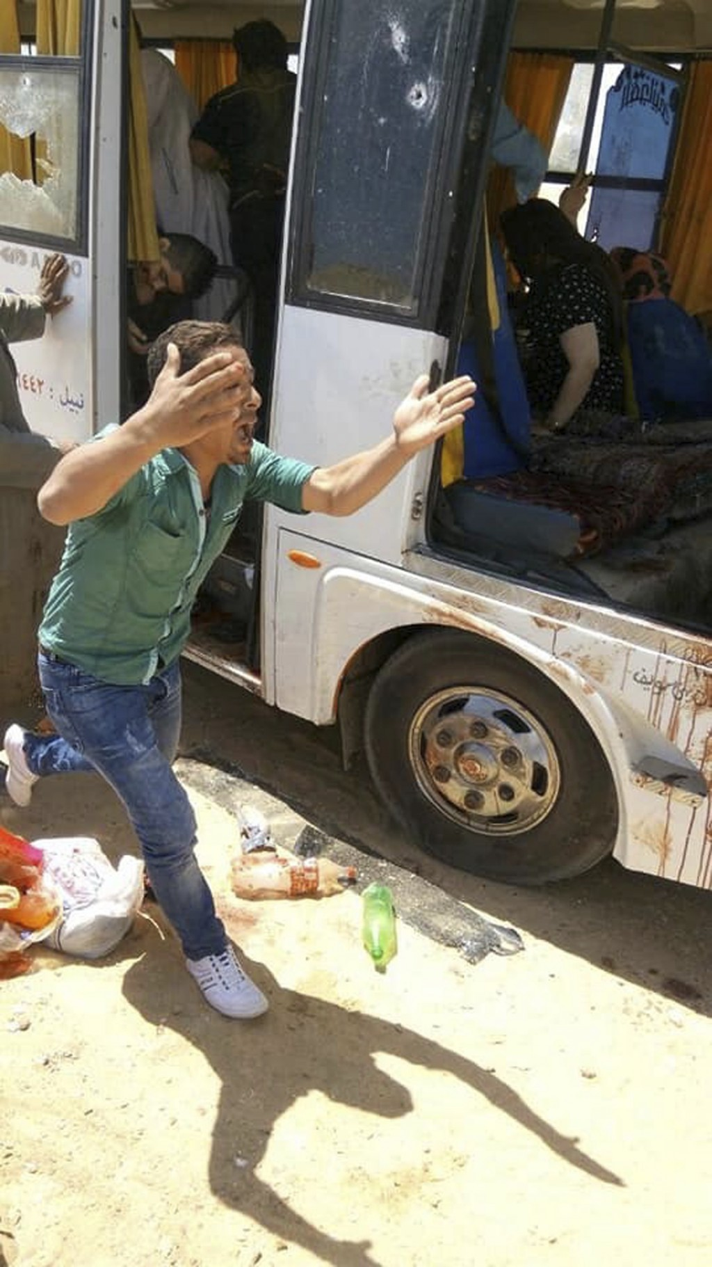 A man screams beside a bus carrying Coptic Christians which came under attack outside Cairo, Friday, Nov. 2, 2018. Islamic militants on Friday ambushe
