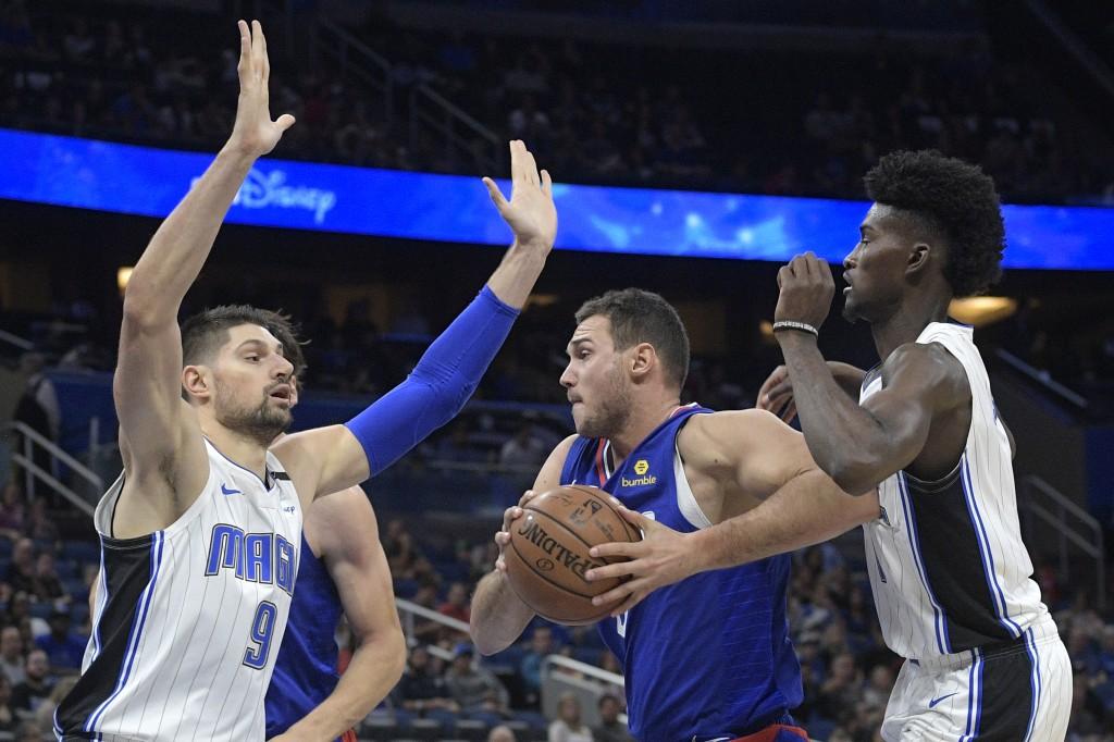 Los Angeles Clippers forward Danilo Gallinari, center, drives to the basket between Orlando Magic center Nikola Vucevic (9) and forward Jonathan Isaac...