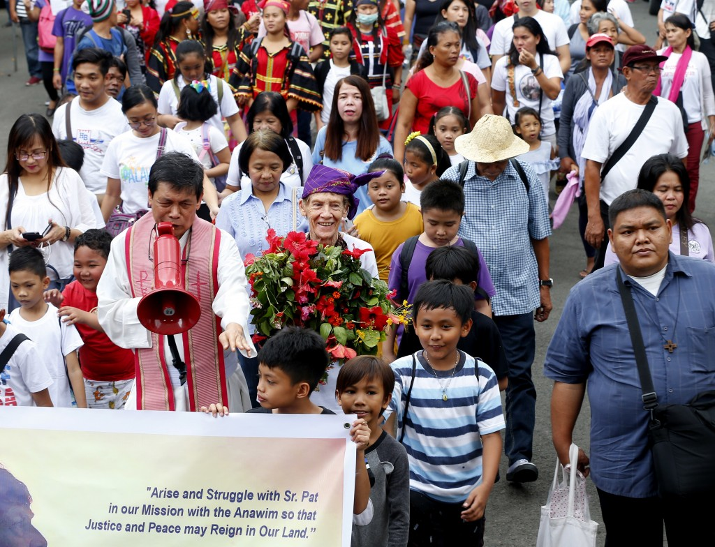 Australian Roman Catholic nun Sister Patricia Fox, center, carries a bouquet of flowers for offering to the image of Our Lady of Perpetual Help during...