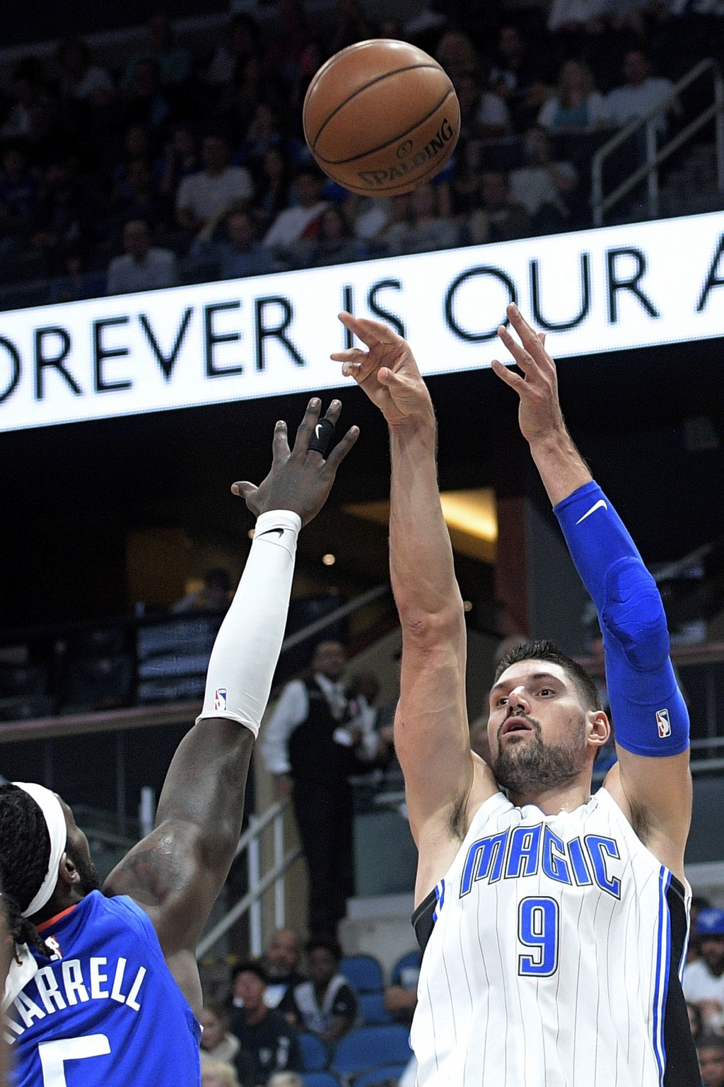 Orlando Magic center Nikola Vucevic (9) goes up for a shot in front of Los Angeles Clippers forward Montrezl Harrell (5) during the first half of an N