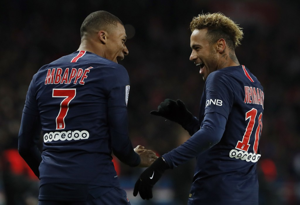 PSG's Kylian Mbappe, left, reacts with PSG's Neymar, celebrating after he scored his side's second goal during the League One soccer match between Par...