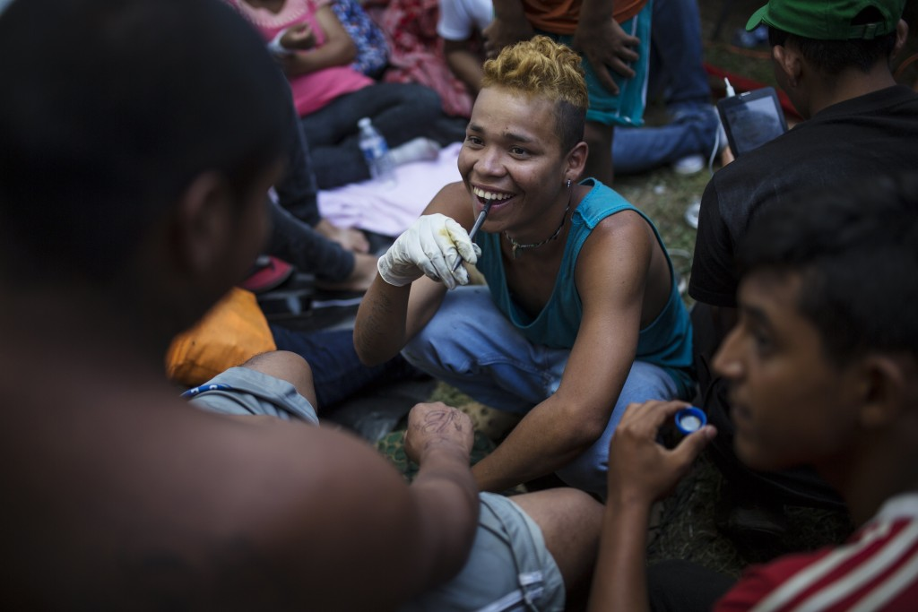 In this Oct. 31, 2018 photo, Honduran Migrant Jose Manuel de Jesus Sandoval laughs while preparing a tattoo on fellow Guatemalan migrant Felix Bautist...