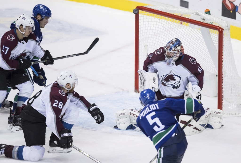 Vancouver Canucks' Derrick Pouliot (5) puts a shot off the post behind Colorado Avalanche goalie Philipp Grubauer (31), of Germany, but has it bounce