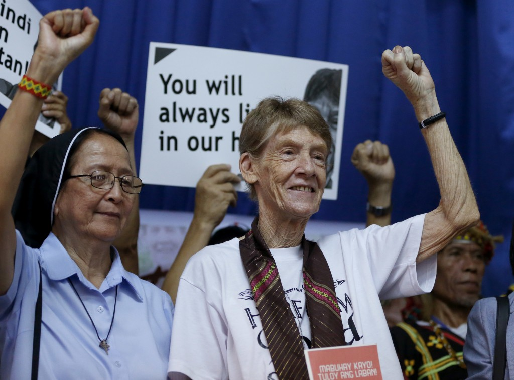Australian Roman Catholic nun Sister Patricia Fox, right, clenches her fist following a news conference hours before her departure for Australia Satur