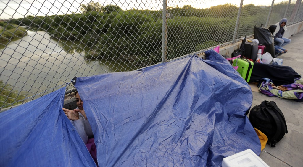 Maidelen Gonzales, an immigrant from Honduras seeking asylum in the United States, waits under a tarp on the Brownsville and Matamoros International B