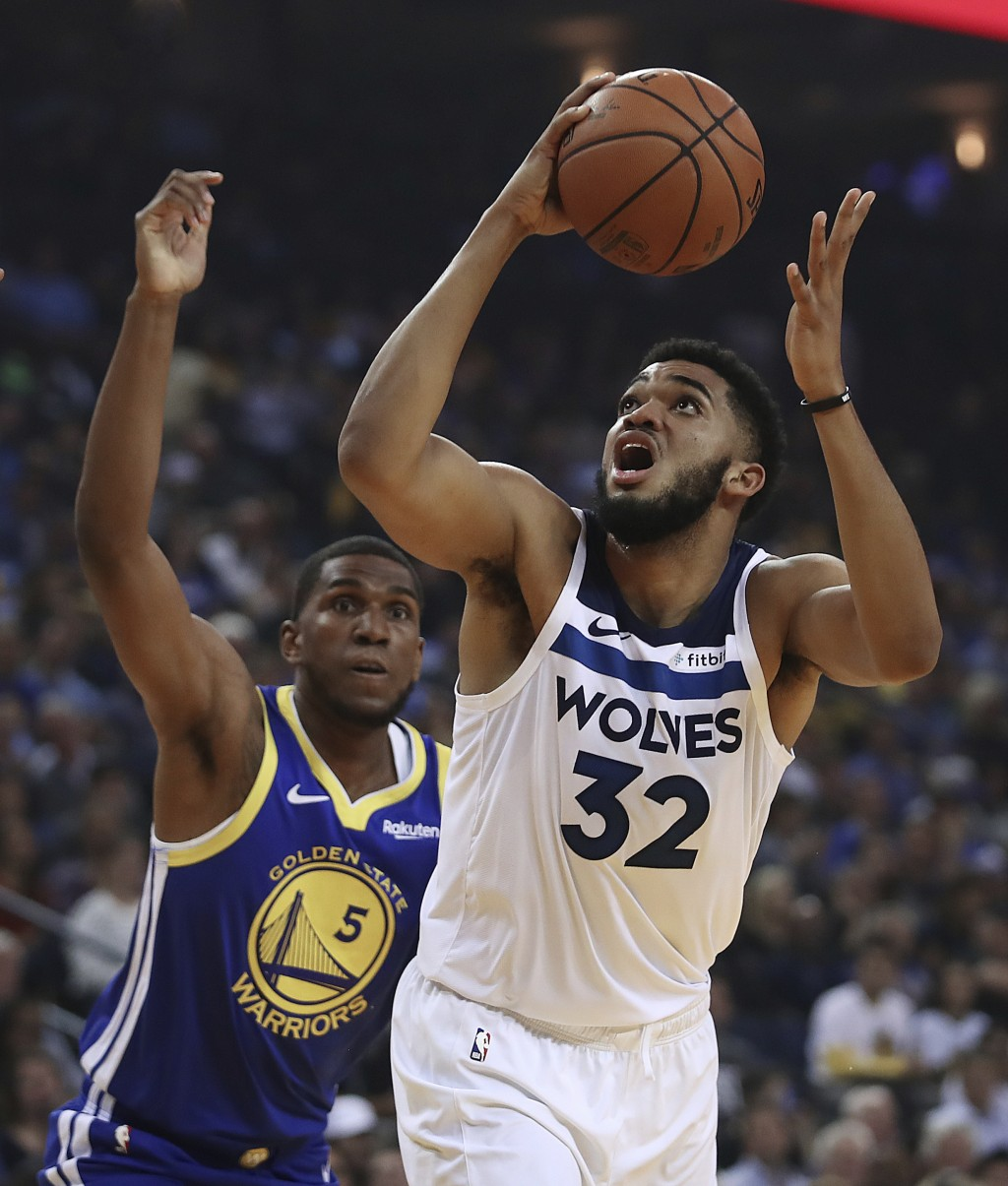 Minnesota Timberwolves' Karl-Anthony Towns, right, looks for a shot next to Golden State Warriors' Kevon Looney (5) during the first half of an NBA ba...