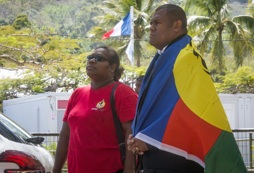 A man, right, drapes the flag of New Caledonia on his shoulders as the French flag flies in the background as he and a woman line up to cast their vot