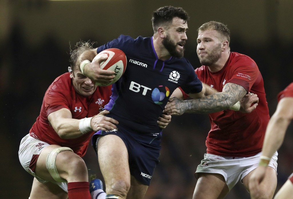 Scotland's Alex Dunbar is tackled by Wales' Alun Wyn Jones, left, and Ross Moriarty during the rugby union international match at The Principality Sta...