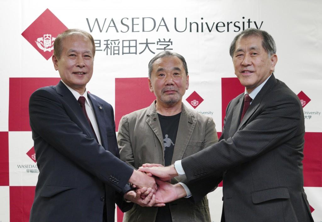 Japanese novelist Haruki Murakami, center, poses for photographers with Kaoru Kamata, left, outgoing president of Waseda University, and incoming pres...