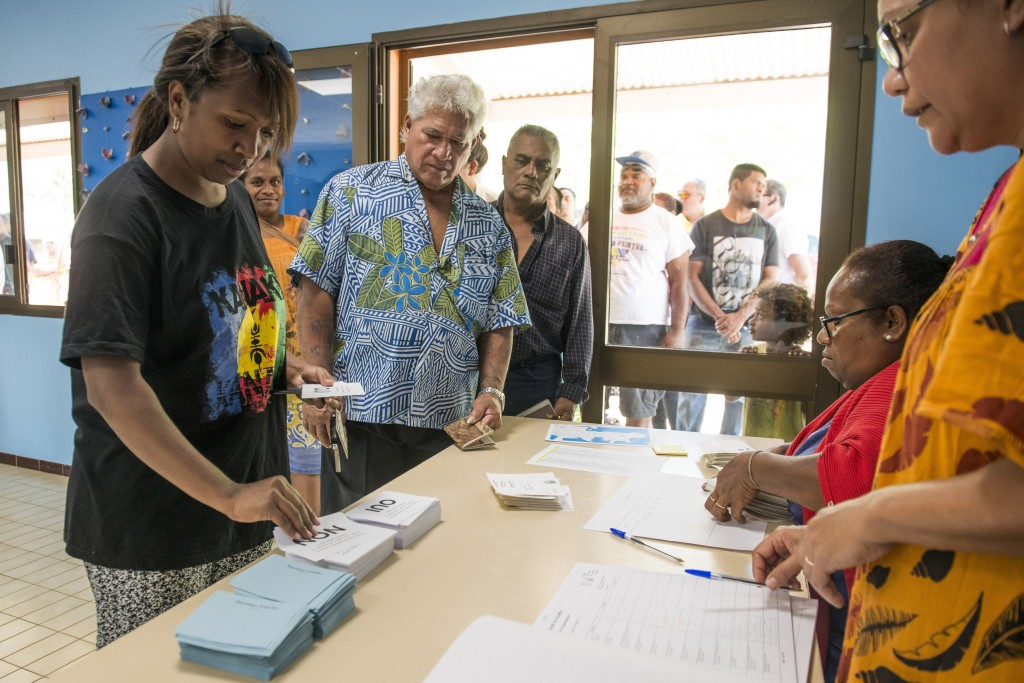 People line up at a polling station in Noumea, New Caledonia, as they prepare to cast their votes as part of an independence referendum, Sunday, Nov.