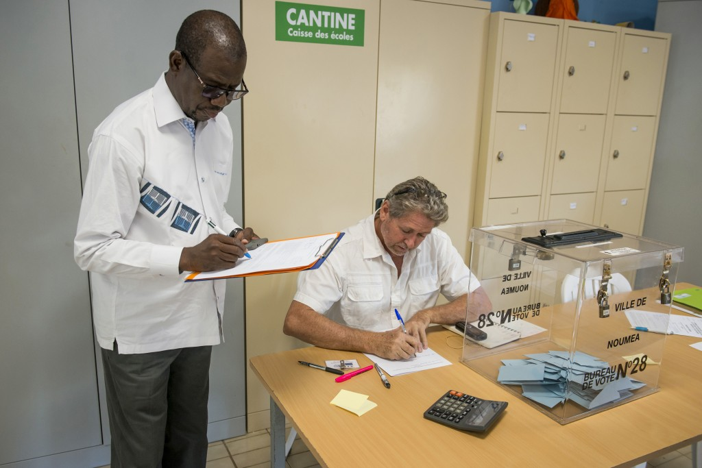 An United Nations observer inspects a polling station while residents in Noumea, New Caledonia, vote as part of an independence referendum, Sunday, No