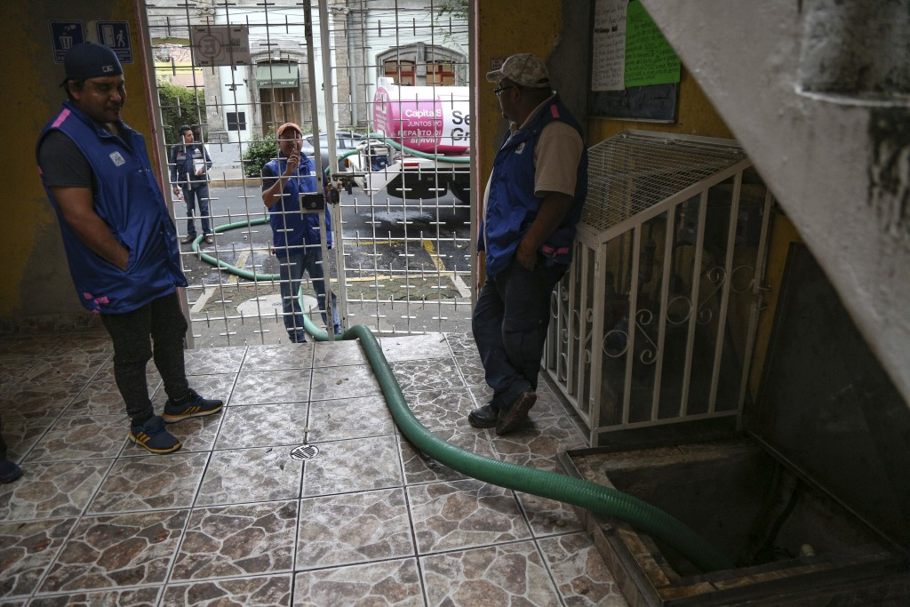 Mexico City Water Systems employees monitor the transfer of water into the apartments water tank in Mexico City, Saturday Nov. 3, 2018. Mexico City is