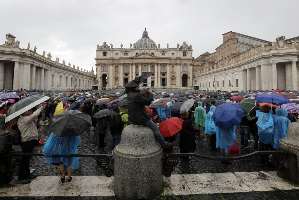 Faithful gather in St. Peter's Square under pouring rain as Pope Francis recites the Angelus noon prayer, at the Vatican, Sunday, Nov. 4, 2018. (AP Ph