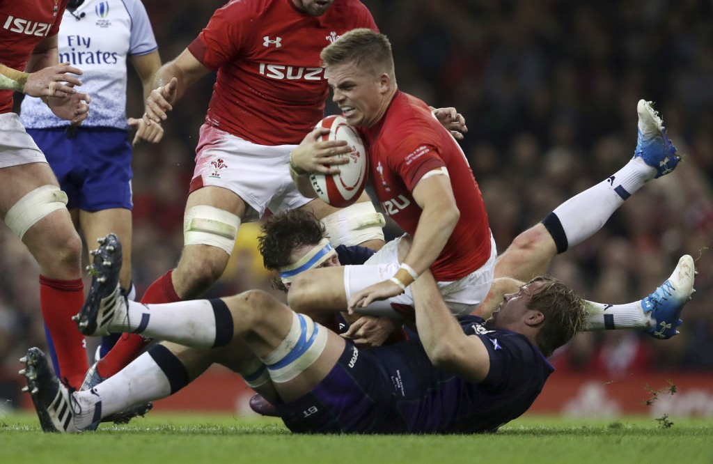 Wales' Gareth Anscombe is tackled by Scotland's Jonny Gray and Hamish Watson during the rugby union international match at The Principality Stadium, C...