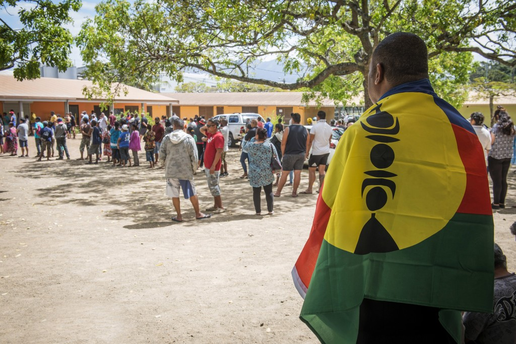 A man drapes his country's flag over his shoulders as residents of New Caledonia's capital, Noumea, wait in line at a polling station before casting t