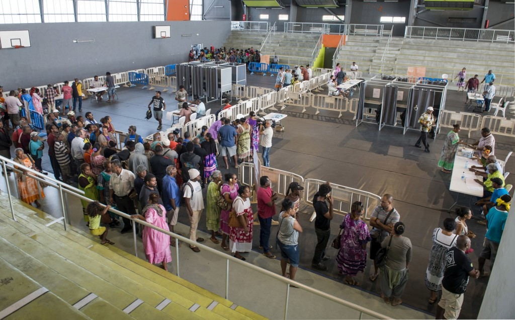 Residents of New Caledonia's capital, Noumea, wait in line at a polling station dedicated to the natives of the Loyalty islands, before casting their