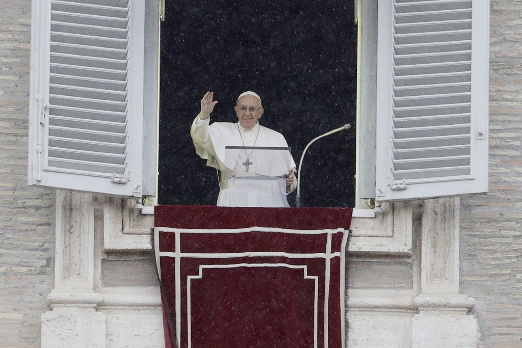 Pope Francis waves to faithful during the Angelus noon prayer he delivered from his studio's window overlooking St. Peter's Square at the Vatican, Sun