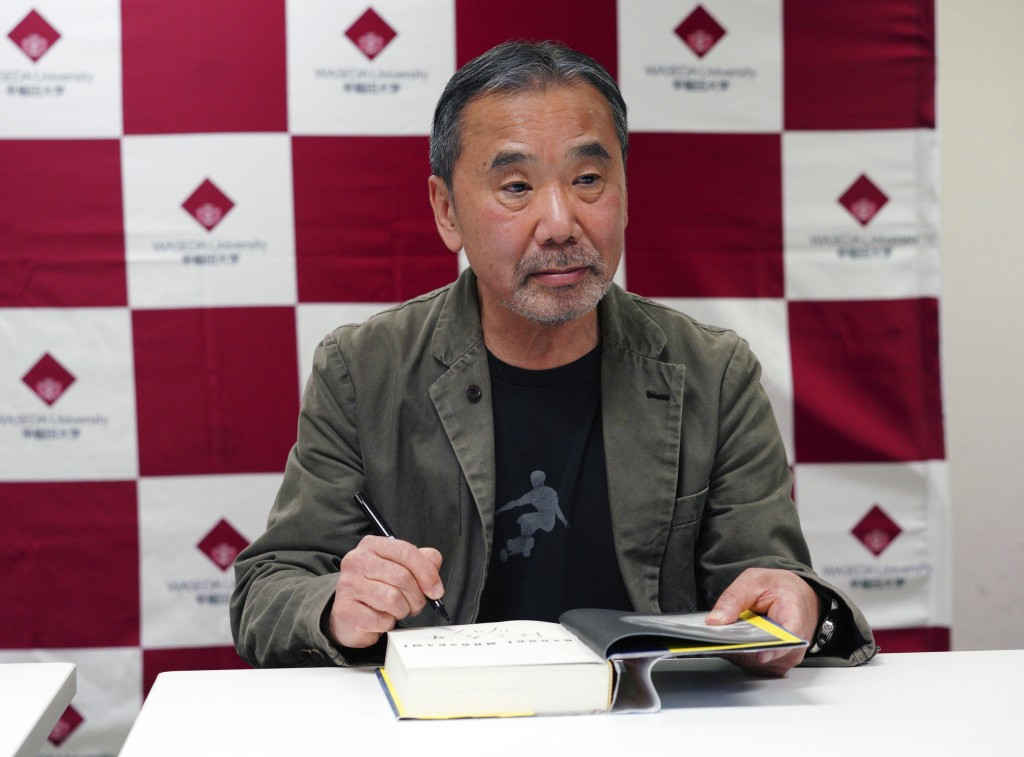 "Japanese novelist Haruki Murakami signs his autograph on his novel ""Killing Commendatore"" during a press conference at Waseda University in Tokyo Satu"