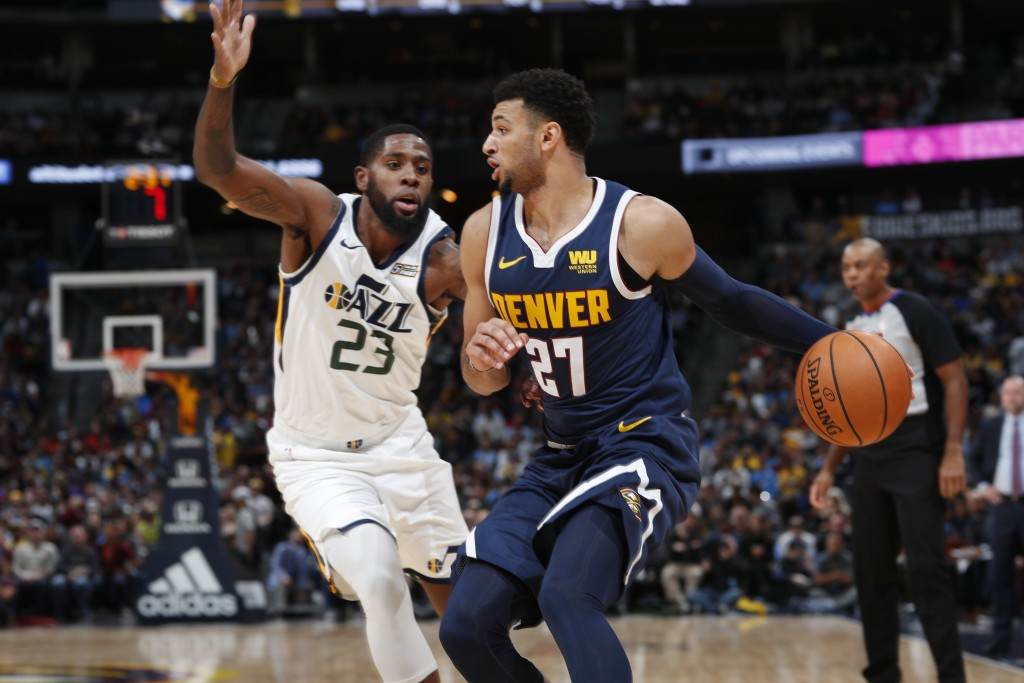Denver Nuggets guard Jamal Murray, right, looks to pass the ball as Utah Jazz forward Royce O'Neale defends during the first half of an NBA basketball...