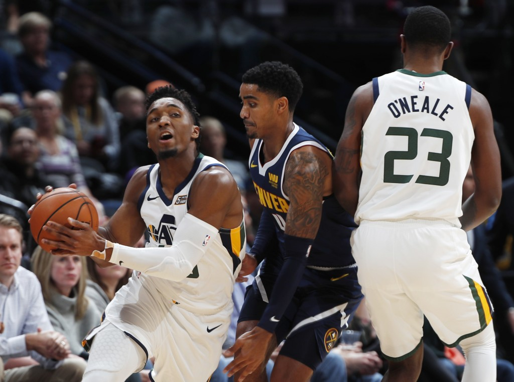 Utah Jazz guard Donovan Mitchell, left, fields a pass as forward Royce O'Neale, right, sets a pick on Denver Nuggets guard Gary Harris during the firs
