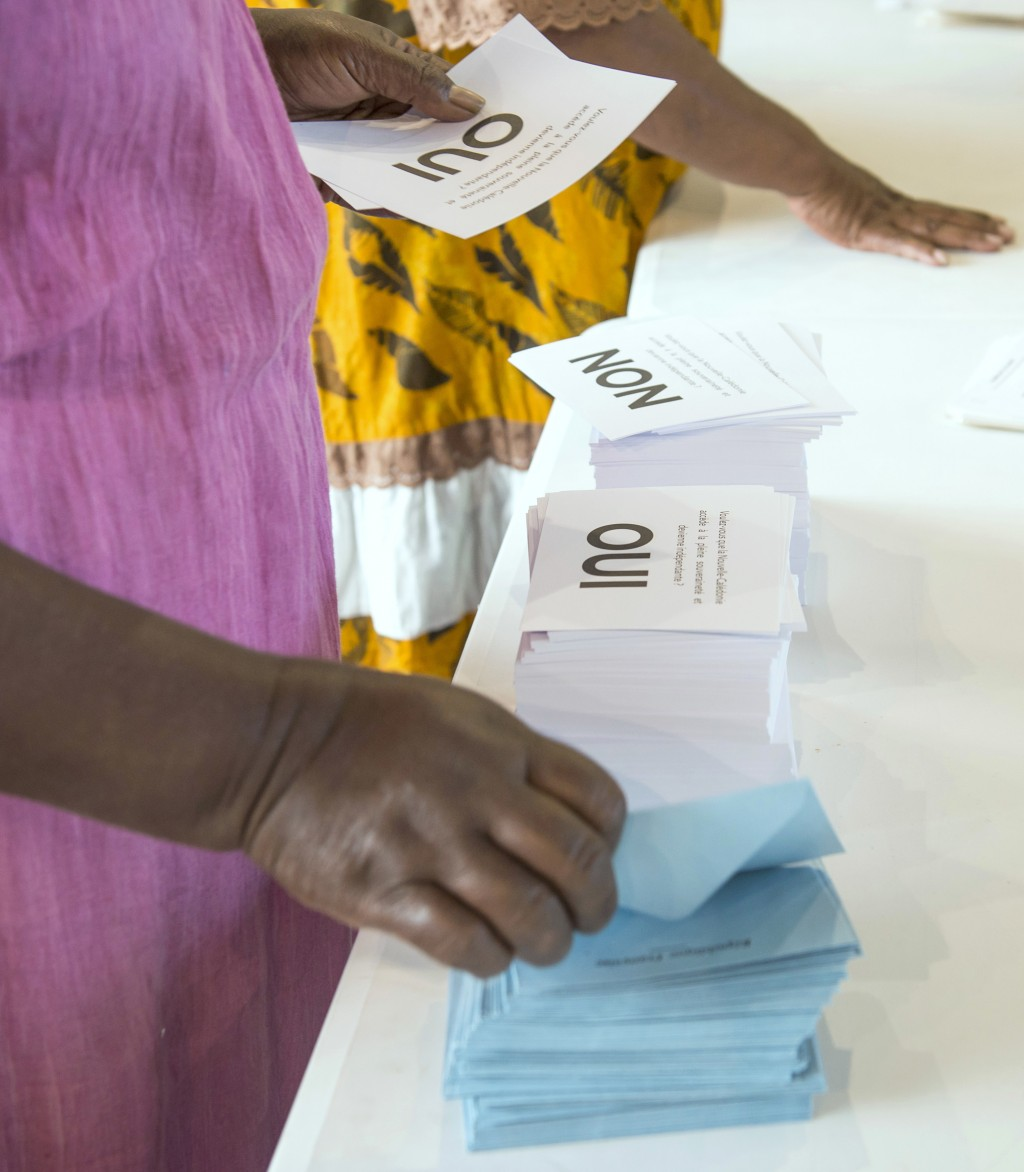 A woman prepares her ballot at a polling station in Noumea, New Caledonia, as part of an independence referendum, Sunday, Nov. 4, 2018. Voters in New