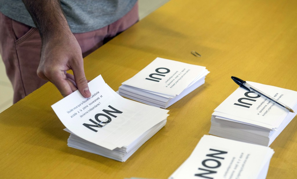 A man prepares to cast his vote at a polling station in Noumea, New Caledonia, as part of an independence referendum, Sunday, Nov. 4, 2018. Voters in