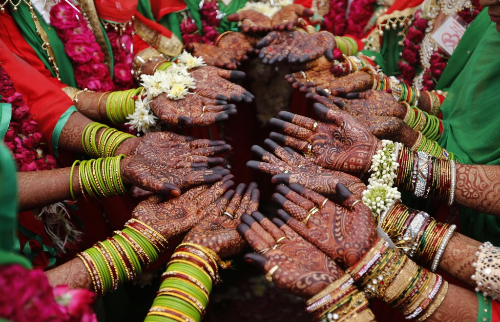 In this Sunday, Nov. 4, 2018, file photo, Indian Muslim brides display henna designs on their hands during a mass marriage in Ahmadabad, India. Thirty