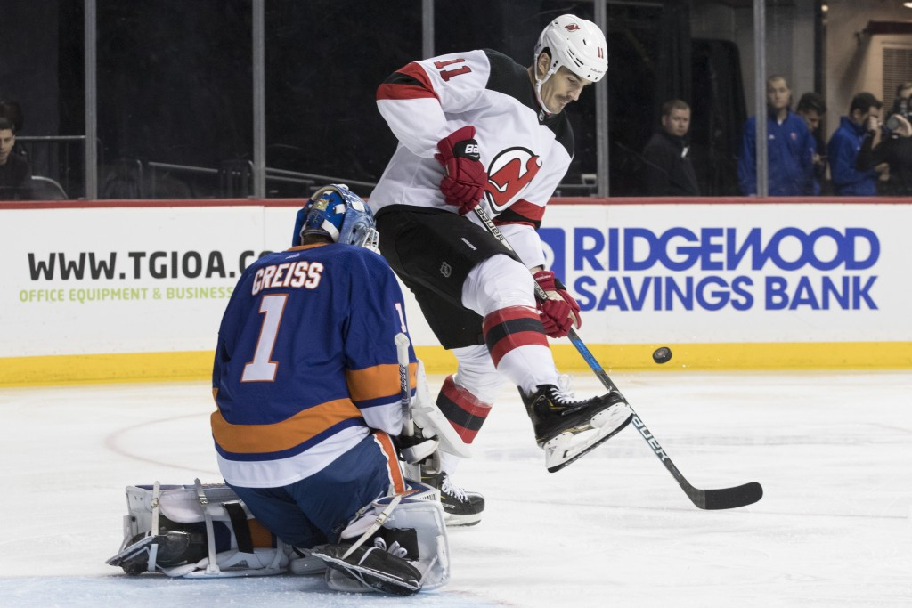 New York Islanders goaltender Thomas Greiss (1) makes a save against New Jersey Devils center Brian Boyle (11) during the first period of an NHL hocke...