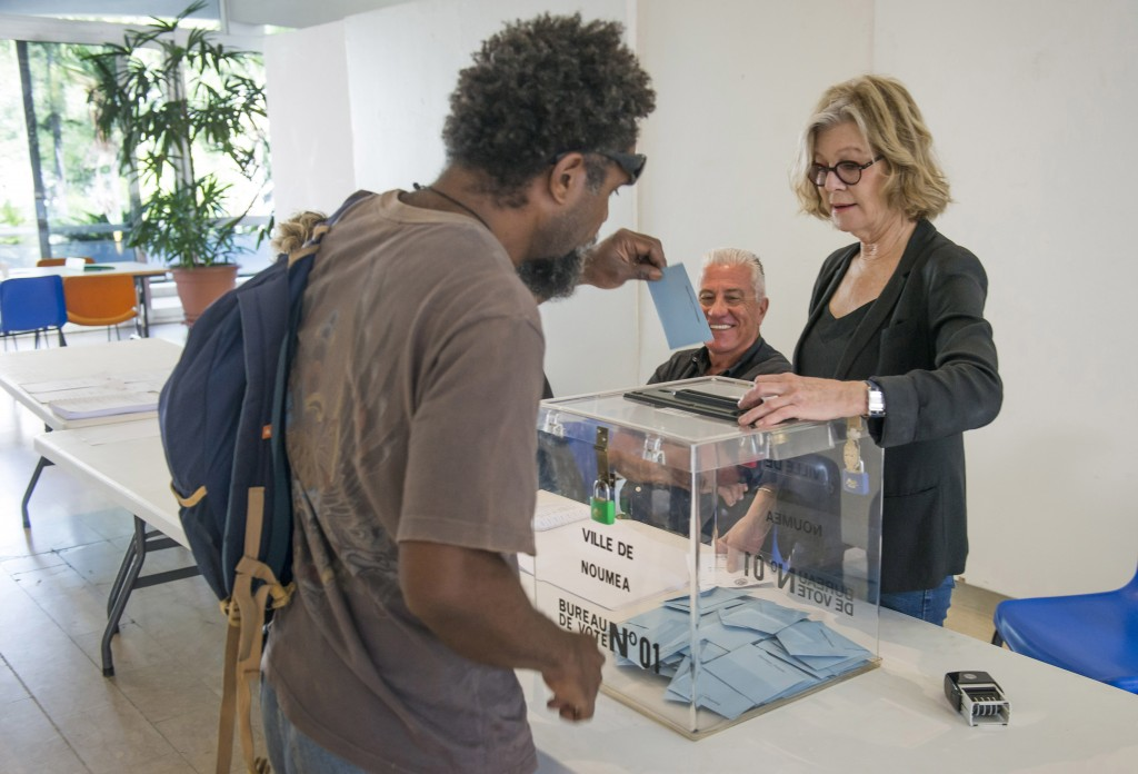 Former Mayor of Noumea, Sonia Lagarde, right, works at a polling station in Noumea, New Caledonia, during an independence referendum, Sunday, Nov. 4, ...