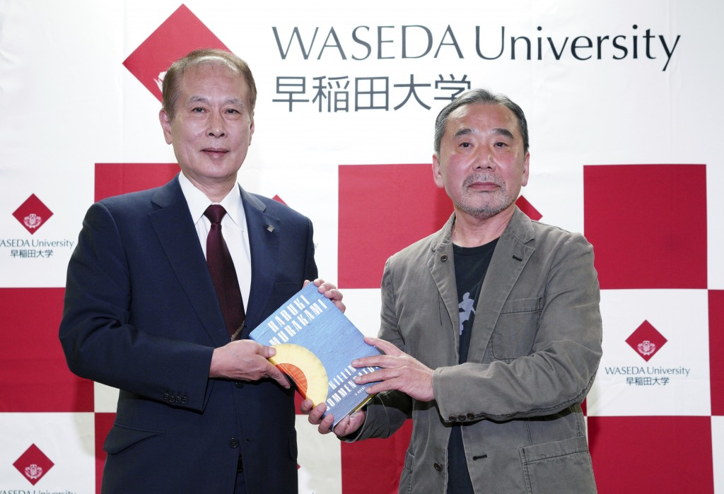 Japanese novelist Haruki Murakami, right, poses for photographers with Kaoru Kamata, left, Waseda's University President during a press conference at