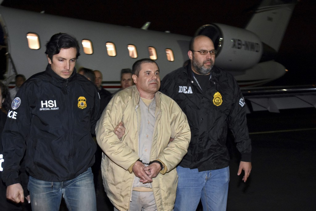 """FILE - In this Jan. 19, 2017 file photo provided by U.S. law enforcement, authorities escort Joaquin """"El Chapo"""" Guzman, center, from a plane to a wait..."""