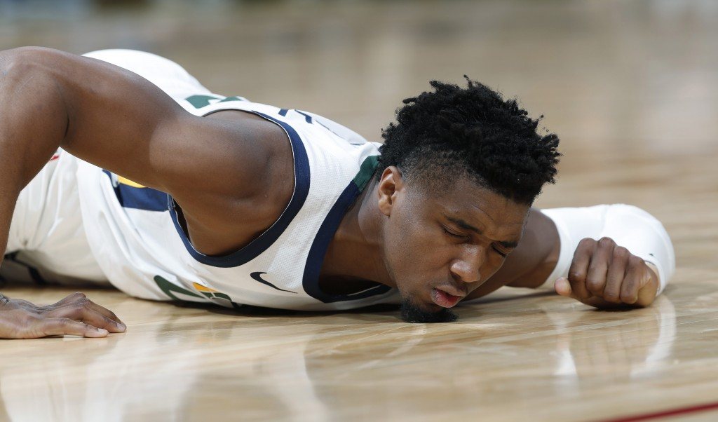 Utah Jazz guard Donovan Mitchell reacts after being injured during the second half of the team's NBA basketball game against the Denver Nuggets on Sat...