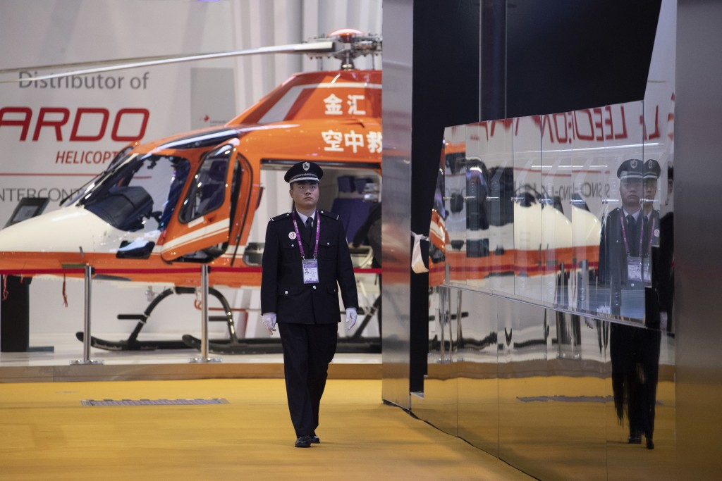 A security guard walks past a helicopter displayed at the China International Import Expo held in Shanghai, Monday, Nov. 5, 2018. Chinese President Xi...