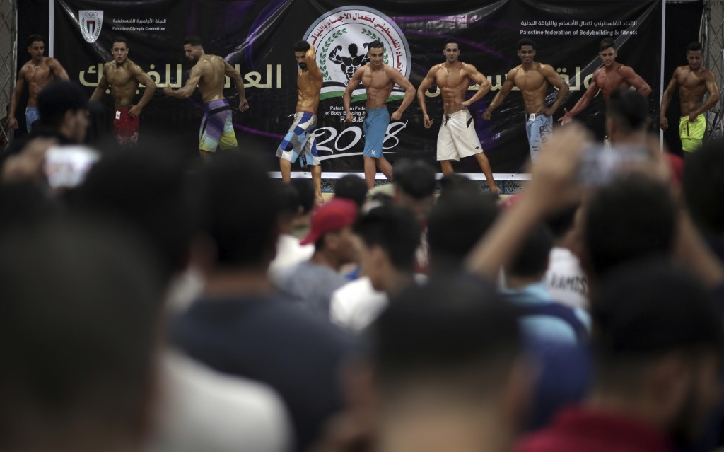 In this Friday, Oct. 26, 2018 photo, Palestinian contestants present their performances on stage during a local bodybuilding competition in Gaza City....