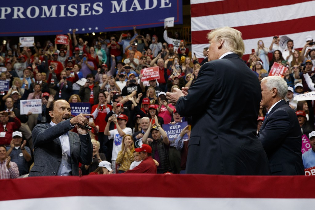 Singer Lee Greenwood points at President Donald Trump and Vice President Mike Pence as he sings during a campaign rally, Sunday, Nov. 4, 2018, in Chat