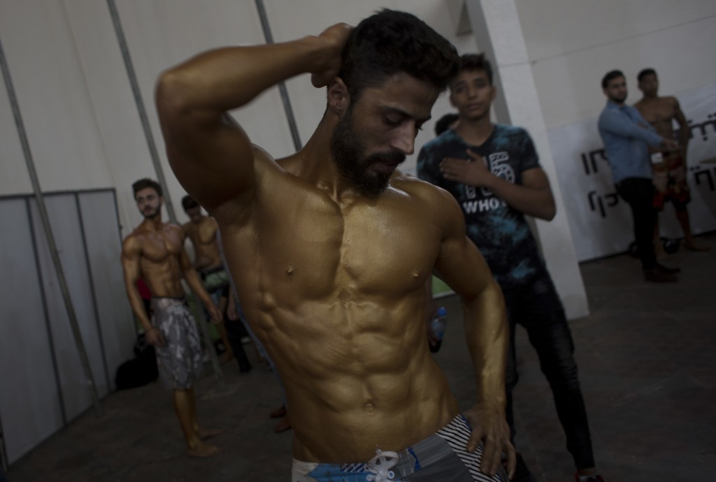 In this Friday, Oct. 26, 2018 photo, a Palestinian bodybuilder prepares himself before giving a performance during a local bodybuilding competition, i...