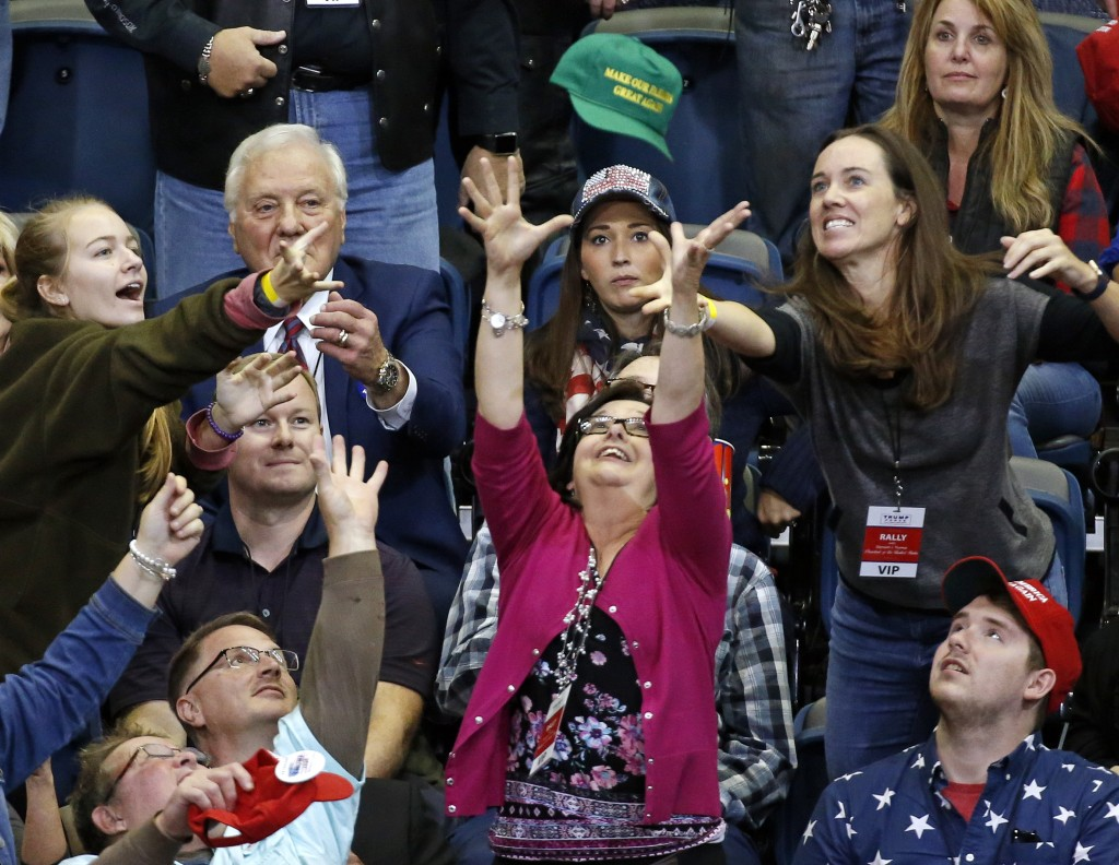 People reach for a cap thrown into the crowd before the start of a rally with President Donald Trump Sunday, Nov. 4, 2018, in Chattanooga, Tenn. (AP P...