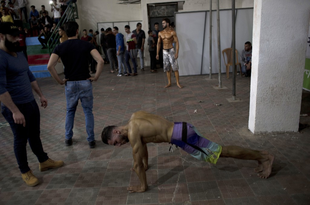 In this Friday, Oct. 26, 2018 photo, Palestinian contestants prepare themselves for a local bodybuilding competition, in Gaza City. In contrast to sim...