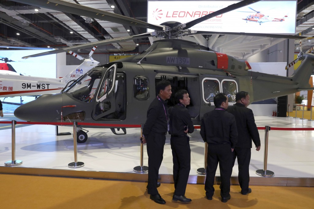 Visitors stand near a helicopter displayed at the China International Import Expo in Shanghai, Monday, Nov. 5, 2018. Chinese President Xi Jinping prom...