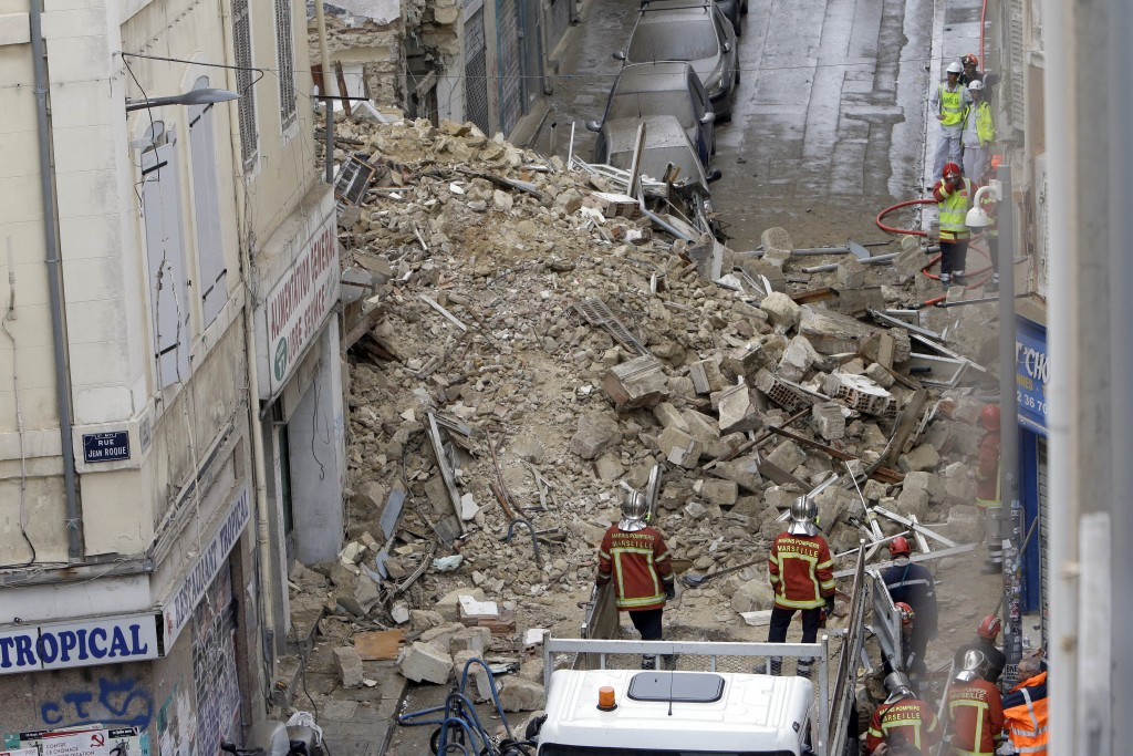 Firefighters work at the scene where buildings collapsed in Marseille, southern France, Monday, Nov. 5, 2018.  Two buildings collapsed in the southern