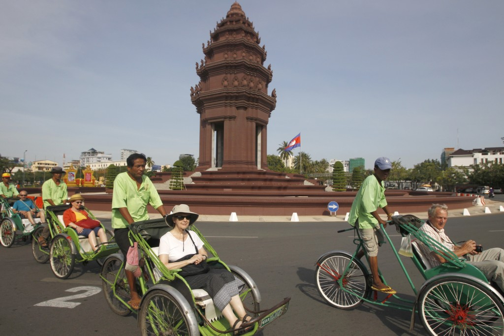 Tourists ride on three-wheeled pedicabs near Independence Monument as they head to Cambodia's Royal Palace in Phnom Penh, Cambodia, Monday, Nov. 5, 20...