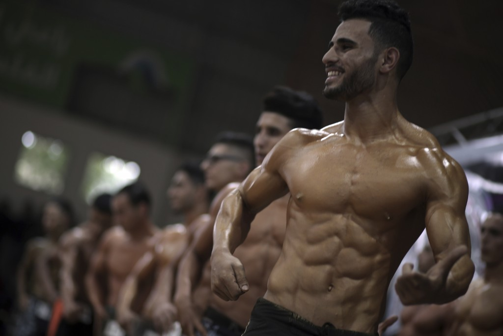 In this Friday, Oct. 26, 2018 photo, Palestinian contestants perform on stage during a local bodybuilding competition, in Gaza City. Glistening with o...