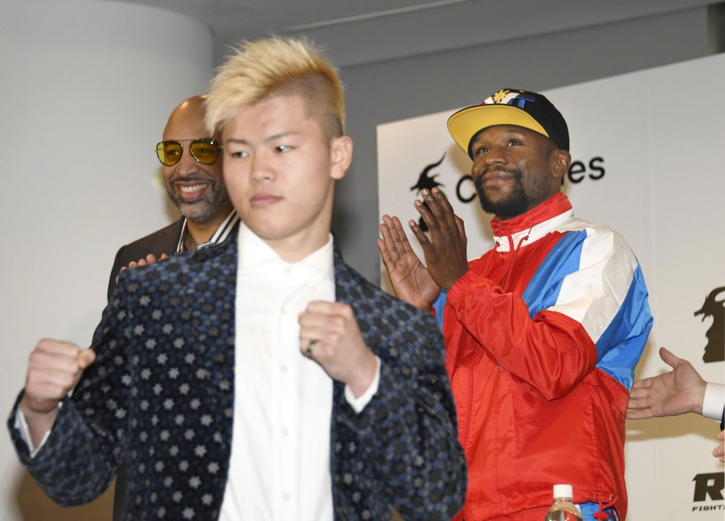 Floyd Mayweather, right, of the U.S. claps as Japanese kickboxer Tenshin Nasukawa strikes a pose during a press conference in Tokyo, Monday, Nov. 5, 2...